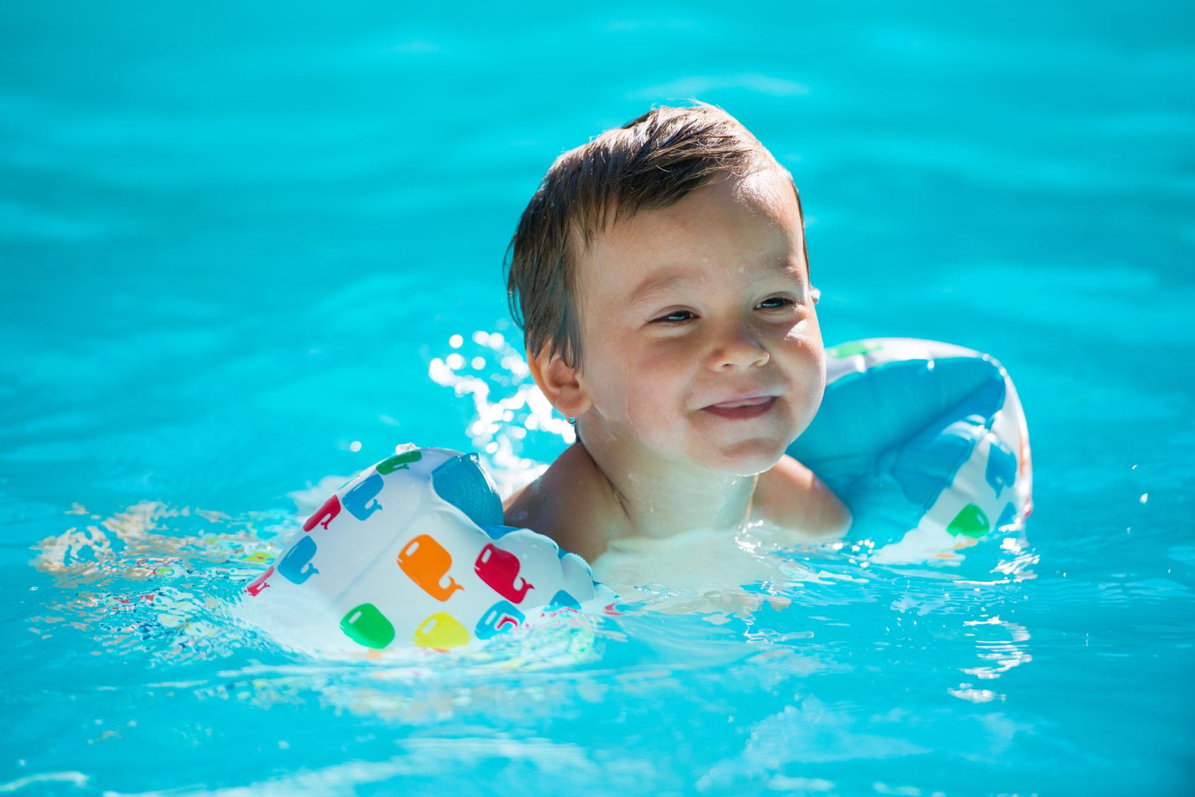 enfant avec des brassards- la piscine
